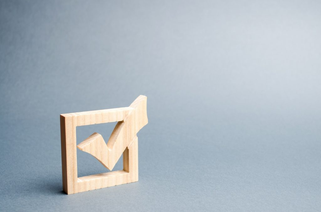 wooden checkmark for voting on elections on a gray background